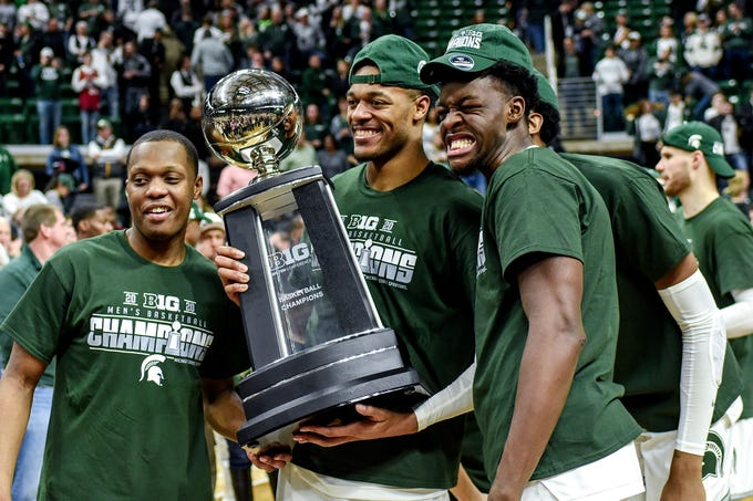 From left, Michigan State's Cassius Winston, Xavier Tillman and Gabe Brown pose with the Big Ten Championship trophy after beating Ohio State on Sunday, March 8, 2020, at the Breslin Center in East Lansing. The Spartans won a share of the title with Maryland and Wisconsin.