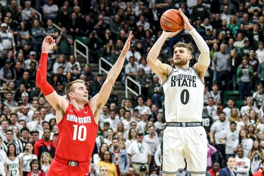 Michigan State's Kyle Ahrens, right, shoots as his brother Ohio State's Justin Ahrens during the second half on Sunday, March 8, 2020, at the Breslin Center in East Lansing.