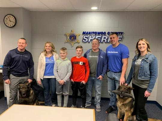 The Mertens family – Geoff, Tammy, Cameron and Carter – deliver a $5,000 check from the Emma Loves Dogs Foundation to the Manitowoc County Sheriff's Office K-9 Unit.