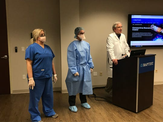 Staff at Baptist Memorial Health Care demonstrate personal protective equipment while Dr. Steve Threlkeld, co-director of the infection control program, right, speaks about coronavirus on Monday, March 9, 2020.