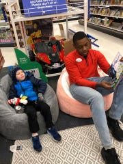 Trey Hawthorne, a 20-year-old employee at Target in Brookfield, is seen here reading a Dr. Seuss book to a child during Target's celebration of National Read Across America Day.