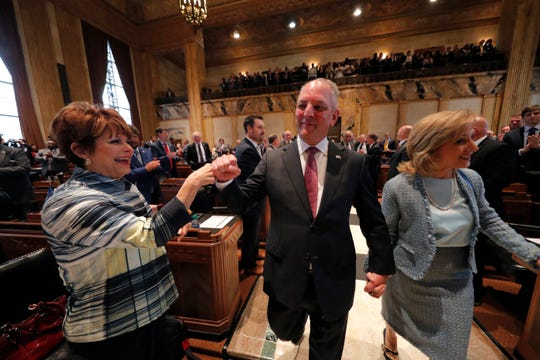 Louisiana Gov. John Bel Edwards bumps fists instead of his traditional handshake with Polly Thomas, R- Metairie, as a precaution against novel coronavirus, as he walks down the aisle of the House Chambers for the opening of the 2020 general legislative session in Baton Rouge, La., March 9, 2020.