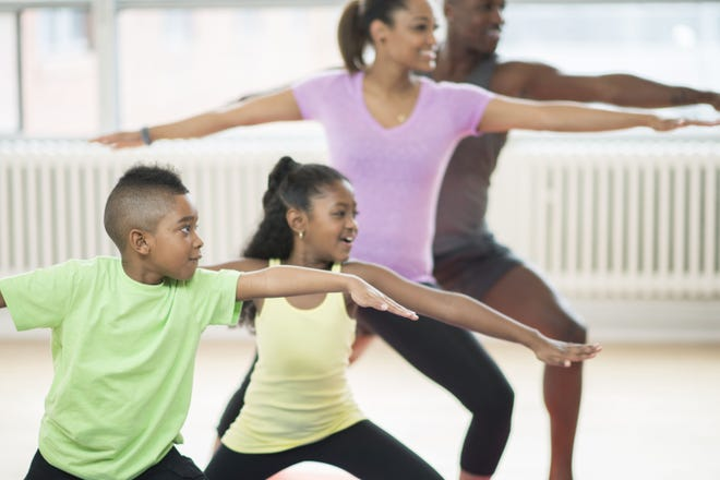 A family of four are holding warrior two pose during a yoga class at the gym. They are wearing athletic clothing and are exercising together as a family.