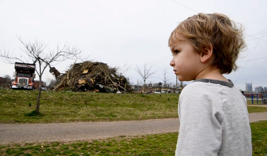 Waylon Morris, 3, watches as trucks load trash while cleaning up tornado damage on Monday, March 9, 2020 in the East Nashville community of Nashville, Tenn.