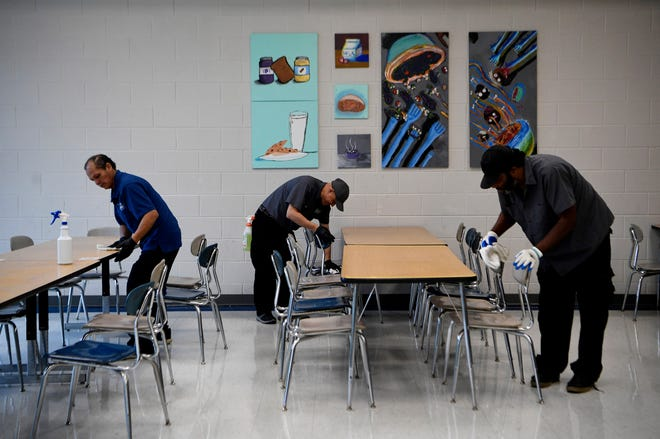 Jose Garcia, left, Leonardo Osorio, center, and Antonio Turner clean the Freedom Middle School lunch room in Franklin, Tenn., on Monday, March 9, 2020, as part of an entire school deep cleaning following the announcement of a coronavirus case in the county.