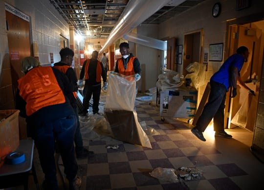 Workers bag up trash and clean the hallway Thursday, March 5, 2020, after a tornado damaged Meigs Academic Magnet School in Nashville.
