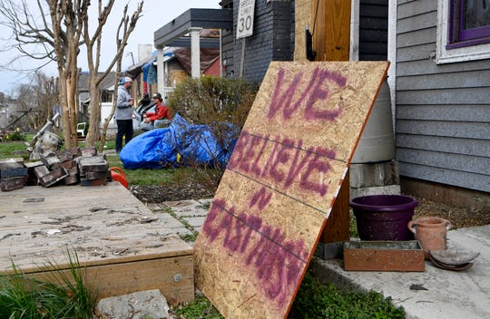 """""""We believe in East Nashville"""" is spray painted on a board outside a home on Monday, March 9, 2020 in Nashville, Tenn., following a tornado that tore through the community on March 3."""