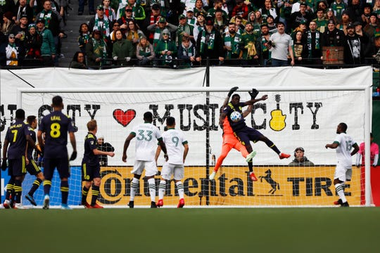 Portland Timbers goalkeeper Jeff Attinella (L) collides with Nashville SC forward Dominique Badji (R) during the second half at Providence Park in Portland, Oregon, on Sunday, March 8, 2020. Mandatory Credit: Soobum Im-USA TODAY Sports