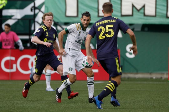 Portland Timbers midfielder Diego Valeri (C) battles for the ball against Nashville SC midfielder Dax McCarty (L) and Walker Zimmerman (R) during the second half at Providence Park in Portland, Oregon, on Sunday, March 8, 2020.