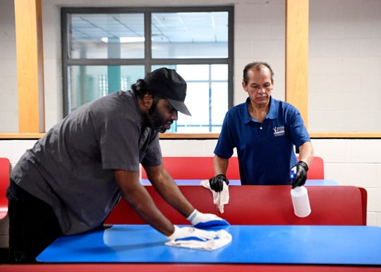Antonio Turner, left, and Jose Garcia wipe down a table at Freedom Middle School in Franklin, Tenn., on Monday, March 9, 2020, as part of deep cleaning following the announcement of a case of coronavirus in Williamson County.
