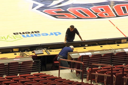 A few UNM workers go over last minute preparations on Monday afternoon at The Pit to get ready for Tuesday's NMAA basketball tournament.