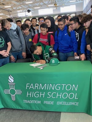 Farmington's Ronald Ladue signs his national letter of intent on Monday to continue his football career at NCAA Division II Fort Lewis College in Durango, Colorado.