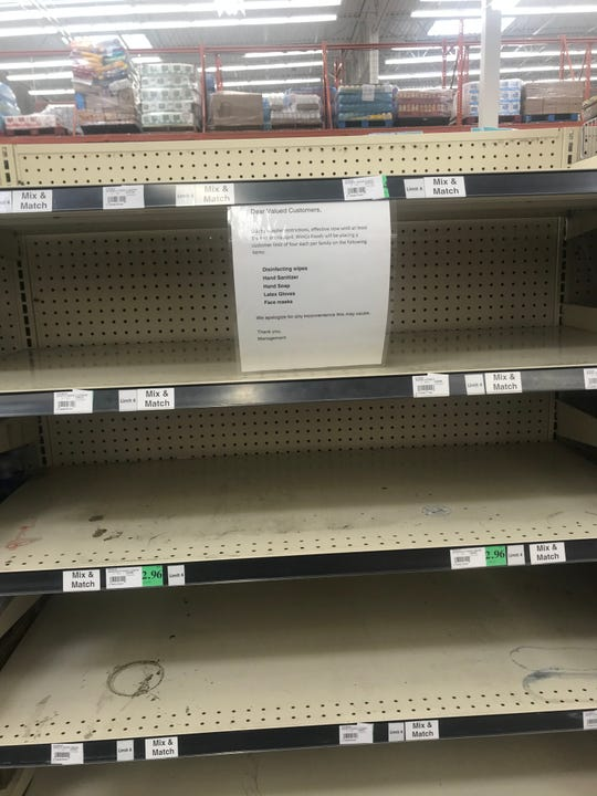 An empty shelf that would normally hold hand sanitizers, latex gloves and face masks is empty at Winco Foods in Indio. The notice says limitations on such items will run through April.