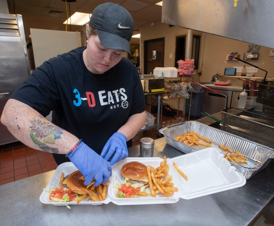 Brooke DeSmet completes a to-go order at the brick and mortar location of 3-D Eats & Tea during the lunch rush Monday.