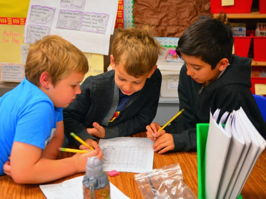 Second graders (from left) Liam Spencer, Carter Ray and Ashton Potter eagerly write answers on the same sheet of paper during a counting exercise.