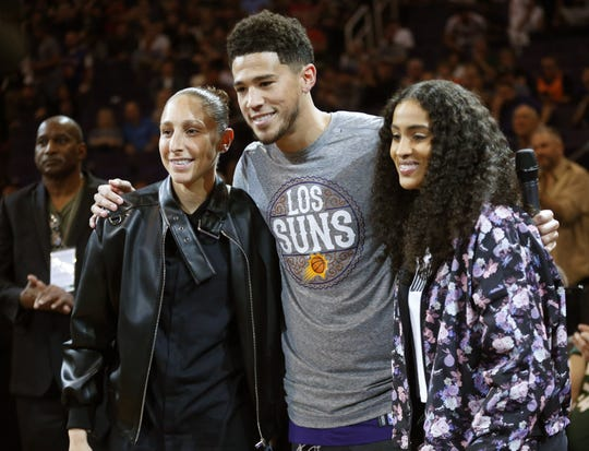 Phoenix Mercury guard Diana Taurasi and forward Skylar Diggins-Smith uses with Phoenix Suns guard Devin Booker before an NBA game between the Phoenix Suns and the Milwaukee Bucks in Phoenix March 8, 2020.