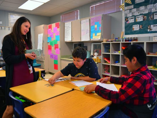 Andrea Steiner talks with fifth graders Damian Green (center) and Jesse Valencia as they add decimals using money.