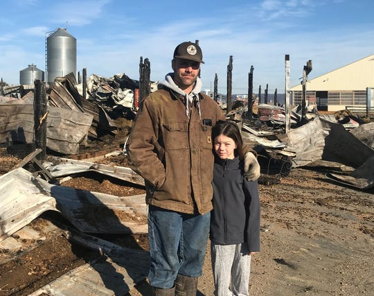 Clovis Crane with his daughter, Dalia, in front of the wreckage from a barn fire. The fire killed 15 horses.
