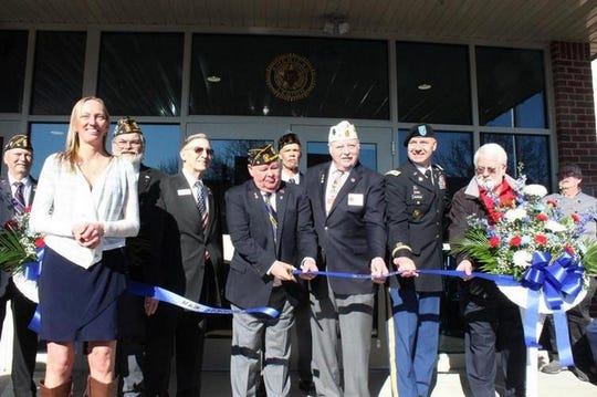 Bill Hoover, commander of American Legion Post 15, cuts a ribbon during Saturday's grand opening celebration for the new headquarters at 63 E. Main St. in Waynesboro.