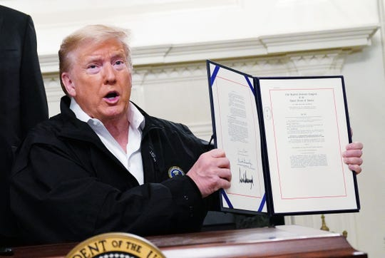 US President Donald Trump holds up an USD 8 billion emergency funding bill to combat COVID-19, coronavirus, after signing it in the Diplomatic Room of the White House in Washington, DC on March 6, 2020. (Mandel Ngan/AFP via Getty Images/TNS)