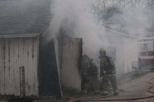 Richmond Fire Department personnel check inside a garage in the 2000 block alley between Glen Court and Grand Boulevard on Monday afternoon.
