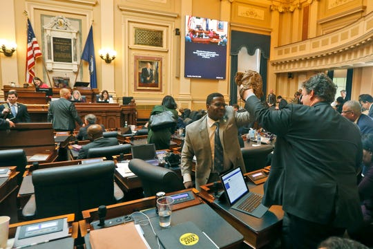 Delegate Alfonzo Lopez, D-Arlington, right, and Delegate Cliff Hayes, D-Chesapeake, give each other high fives with their baseball gloves after the House session at the Capitol on Sunday, March 8 ,  in Richmond.