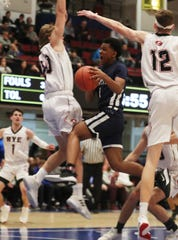Poughkeepsie's Revelation Garriga (1) finds his path to the basket blocked by Rye's C.J. Nemsick (20) during the boys Class  A final at the Westchester County Center in White Plains March 8, 2020. Rye won the game 74-55.