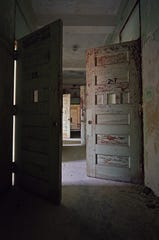 "A hallway of numbered patient quarters at the Norwich State Hospital for the Insane in Connecticut. The image is from ""Abandoned Asylums of The Northeast,"" by Rusty Tagliareni and Christina Mathews."