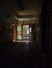 "Standing in a shaded corridor of Rockland Psychiatric, looking toward a common room.  The image is from ""Abandoned Asylums of The Northeast,"" by Rusty Tagliareni and Christina Mathews."