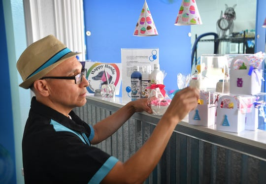 Henry Hernandez, owner of Paw Spa Splash, arranges a display of products for pets including, dog treat bon-bons, canine cologne, bandanas, dental products and more.