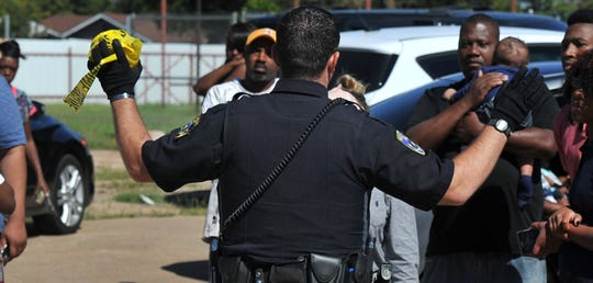 A Wichita Falls police officer tries to calm a crowd of bystanders when things get tense at the scene of a double homicide on Oct. 10, 2016, in the 1300 block of North Third Street.