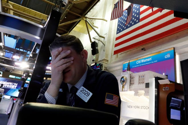 Trader Michael Gallucci prepares for the day's activity on the floor of the New York Stock Exchange, Monday, March 9, 2020. Trading in Wall Street futures has been halted after they fell by more than the daily limit of 5%.