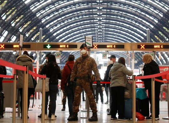 Police officers and soldiers check passengers leaving from Milan main train station, Italy, Monday, March 9, 2020.