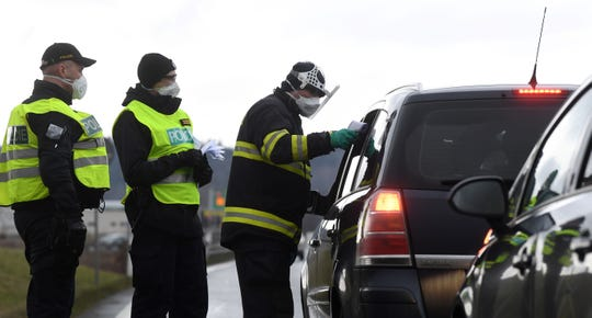 A Czech police officer with a protective mask checks the temperature of a driver during sanitary checks at the border crossing between Germany and the Czech Republic on March 9, 2020.