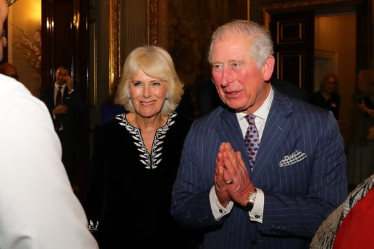 Prince Charles, accompanied by his wife, Duchess Camilla of Cornwall, greets guests with a namaste gesture at a Commonwealth Day reception on March 9, 2020 in London.