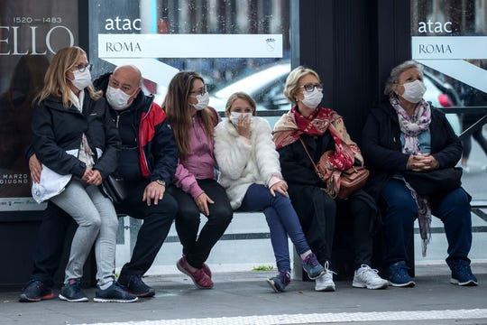 People wait at a bus stop, in Rome, Monday, March 9, 2020.