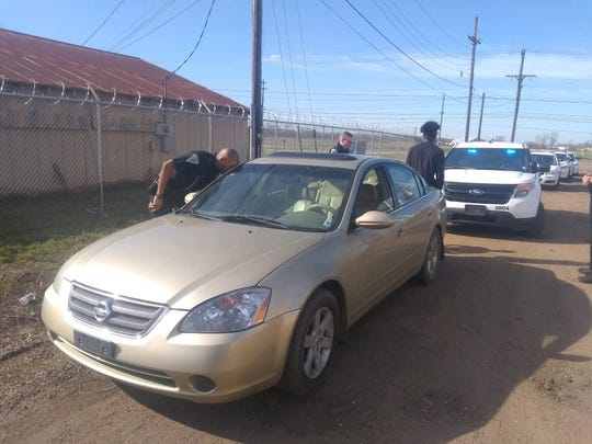 A Natchitoches Parish Sheriff's deputy looks inside a gold Nissan Altima on Sunday after a robbery and stabbing were reported. A Natchitoches man later was arrested.