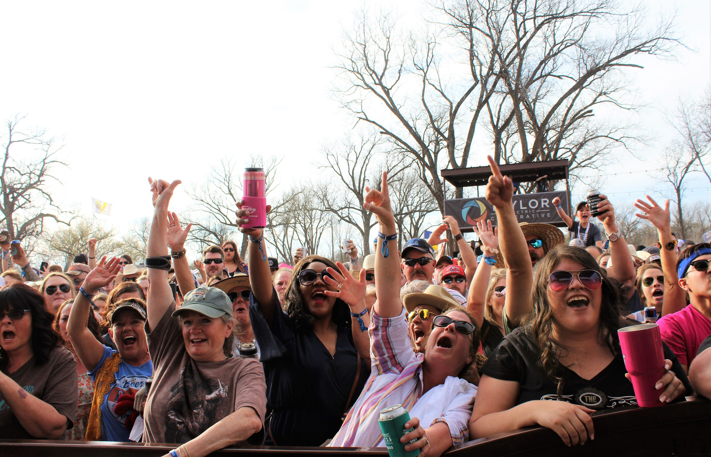Outlaws attendees raise their hands and cans during Kevin Fowler's performance at the 2019 event. Fowler returns for an evening show this year, promising to play all his beer-drinking favorites.