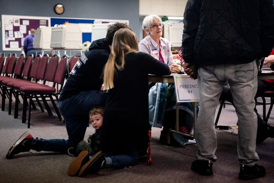 One-year-old Greyson Goras peeks his head out from behind his parents Alex Goras and Savannah Almarez as they enter the polls at Christ United Methodist Church on Tuesday, March 10, 2020 in Battle Creek. Battle Creek voters selected presidential candidates and voted on two proposals, one that would change how the mayor is elected and one that would change the city charter to use ungendered language.