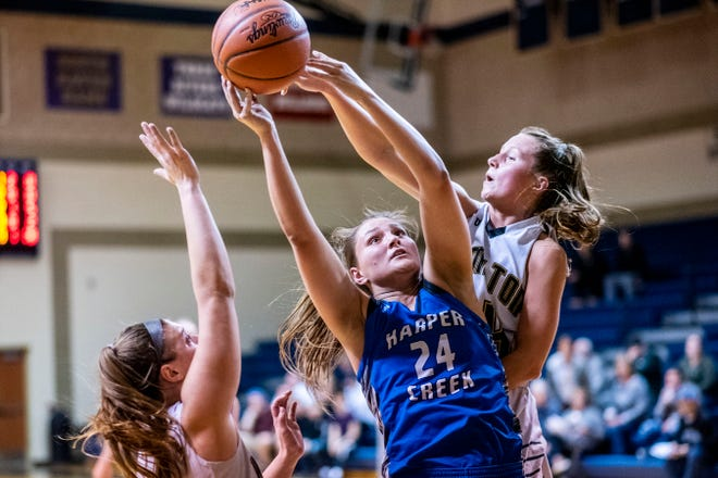 Harper Creek senior Maddie Alexander (24) grabs the rebound from Hamilton junior Sierra Schrotenboer (14) and Hamilton senior Sally Merrill (24) during the Division 2 girls basketball regional semifinal on Tuesday, March 10, 2020 at Otsego High School in Otsego, Mich.