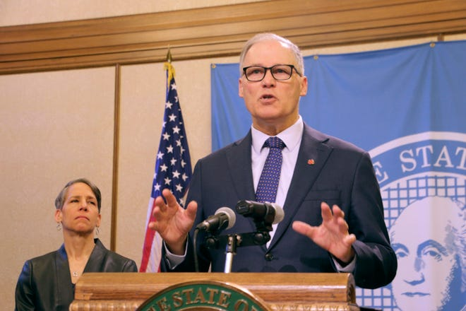 Washington Gov. Jay Inslee, right, talks to the media about the latest actions the state is taking to respond to the coronavirus outbreak, Tuesday in Olympia. Inslee announced a list of requirements for long-term care facilities and new rules related to the unemployment insurance program for workers impacted by COVID-19.