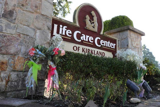 Flowers left next to the sign that marks the entrance to the parking lot of the Life Care Center in Kirkland, Wash. are shown Monday, March 9, 2020, near Seattle. The nursing home is at the center of the outbreak of the COVID-19 coronavirus in Washington state.