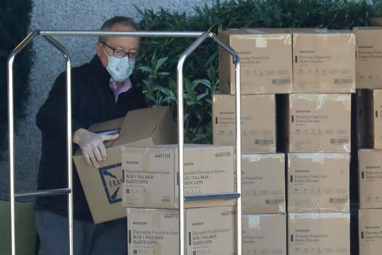 A worker wears a mask as he loads new supplies of gloves, gowns, and other protective gear onto a cart at the Life Care Center in Kirkland, Wash. Monday, March 9, 2020, near Seattle. The nursing home is at the center of the outbreak of the COVID-19 coronavirus in Washington state.