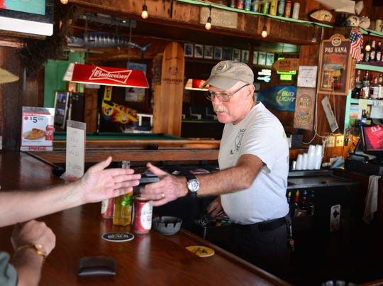 Mike Morrison, who has tended bar at Beach Shack since 1989, serves a customer Tuesday in Cocoa Beach.