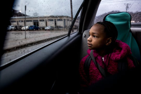 """Amariyonna, 9, looks out the window as her mom drives her and her sisters to school in Northside on Tuesday, February 4, 2020. The girls sing along to various soundtracks on their morning commute. Some of their favorites are """"Frozen"""" and """"The Lion King."""""""