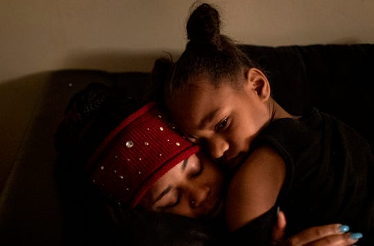 Amariyonna, 9, hugs her mom Page Berry before Berry leaves her Westwood apartment to go to work moving freight on a rainy airport tarmac on Wednesday, February 26, 2020.