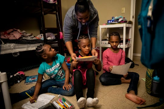 Page Berry helps her three daughters Angelina, 7, Ajaunae, 8, and Amariyonna, 9, with their homework in the girls' bedroom in their basement apartment in Westwood on Tuesday, February 4, 2020.