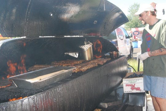 Art Weems of Big Arts BBQ&Grill looks over the ribs on the barbecue at the Taste of Colerain.
