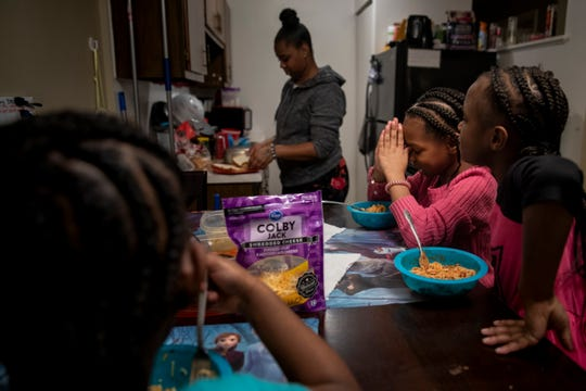 Amariyonna, 9, prays before eating dinner with her sisters and mom in their apartment in Westwood on Tuesday, February 4, 2020.