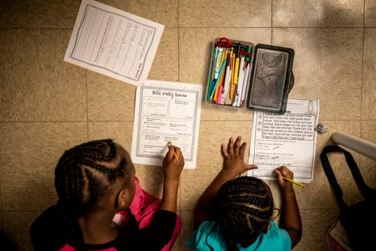 Ajaunae, 8, and Angelina, 7, work on their math and English homework in their bedroom on Tuesday, February 4, 2020.